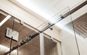 Barn door slider with modern hardware. Upper fasteners and rollers for the sliding glass door in the shower enclosure are joined with the glass to the sauna area.