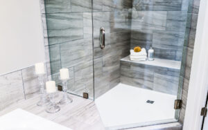 Closeup of modern stone grey tiled bathroom. Corner shower with angled door.