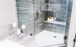 Closeup of modern stone grey tiled bathroom. Corner shower with angled door.