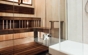 Glass door design in the sauna and shower cabin with metal door hinge in the interior